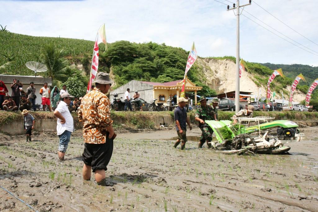 Dr. Hasil Sembiring watches a planting machine demonstration at Perbulan Village of Kabanjahe District.