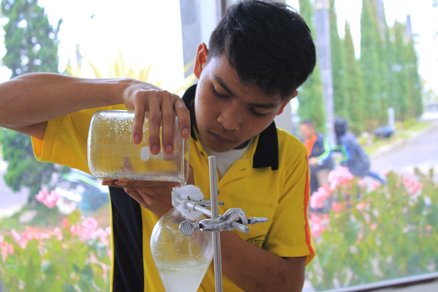 Student's lab work, measuring the oil concentrate as the final step of producing lemongrass oil, another processed product of organic farm.