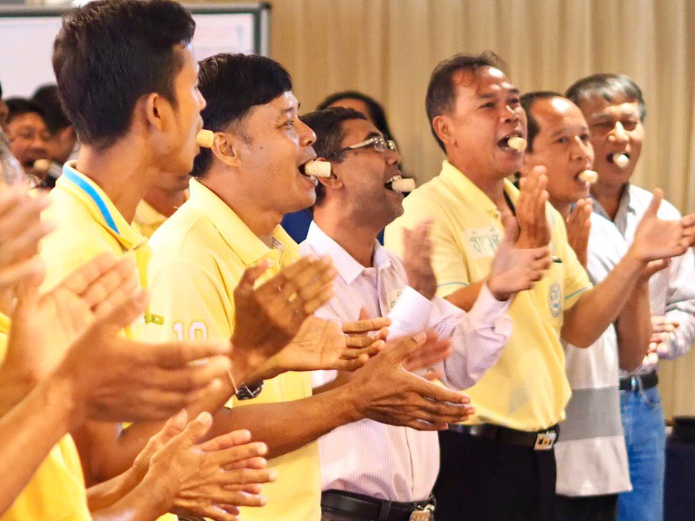 Oil palm growers practice clear pronunciation by holding the wine corks with their mouths while speaking. (Photo credit: GIZ Thailand)