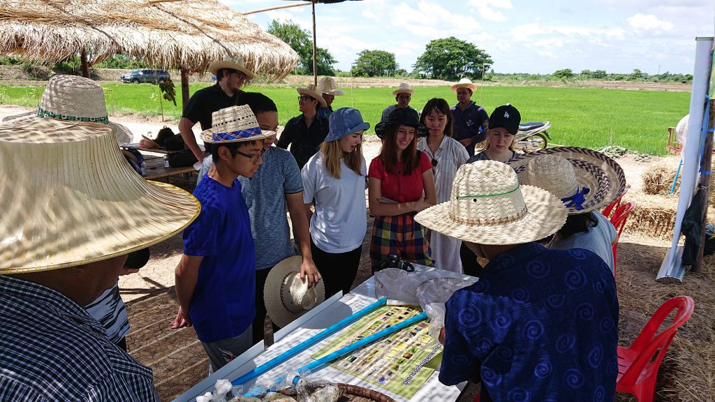 The students listen to a local farmer who explains about sustainable pest management practices. (Photo credit: Tobias Vomberg/ GIZ Thailand)