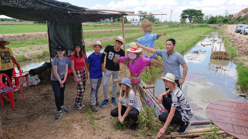 The students pose for a group photo with scarecrows that are made of straw and stand guard over the rice fields. (Photo credit: Tobias Vomberg/ GIZ Thailand)