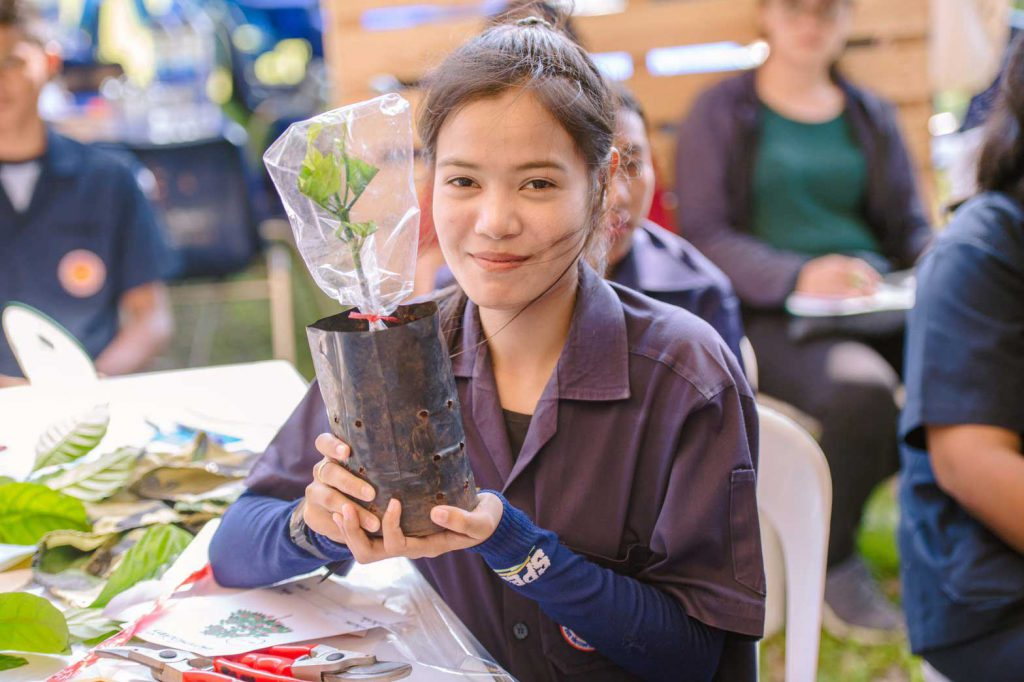 An upper vocational student shows coffee seedling. (Photo credit: GIZ Thailand)