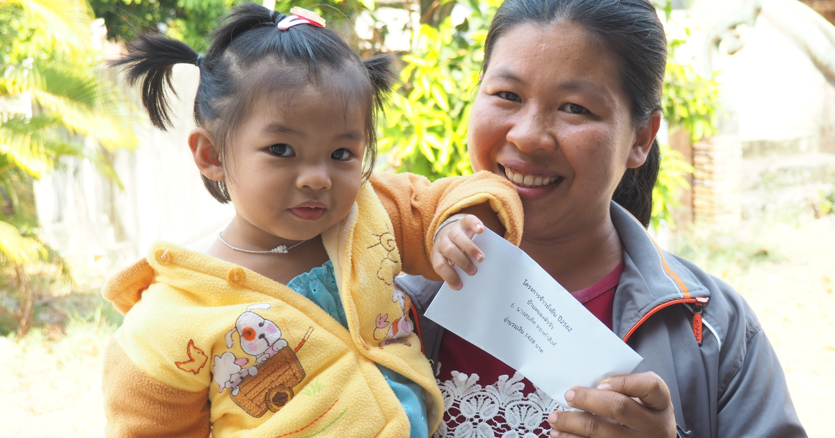 A farmer from Samrong district of Ubon Ratchathani province takes her daughter to the community hall, so they can receive the bonus together. (Photo credit: GIZ Thailand)