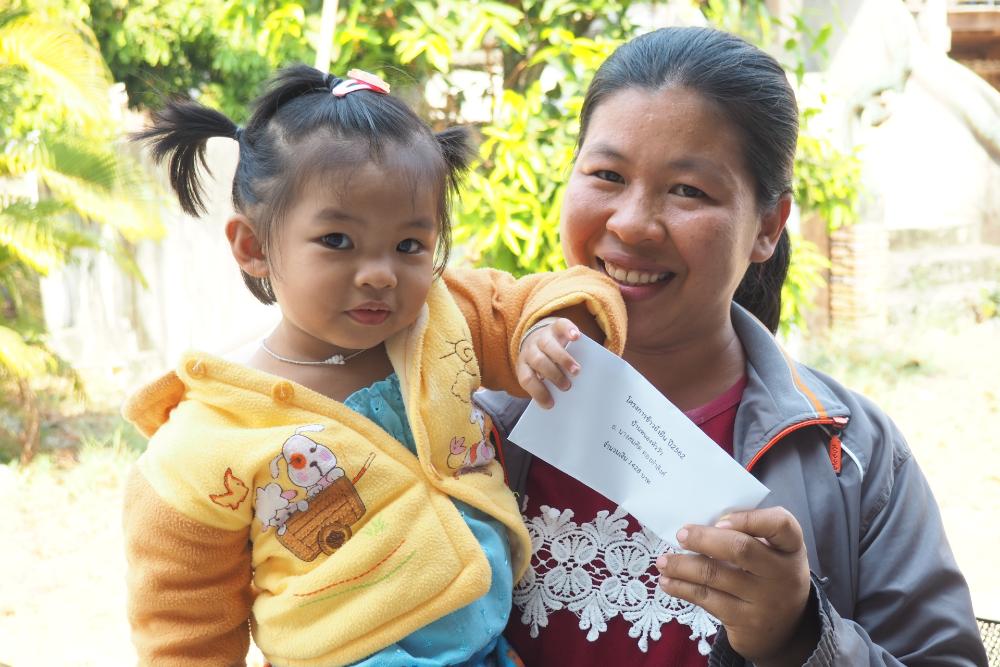 เกษตรกรจากอำเภอสำโรง จังหวัดอุบลราชธานี พร้อมลูกสาว โชว์ซองใส่เงินโบนัสในมือ (เครดิตรูปภาพ: GIZ ประเทศไทย)